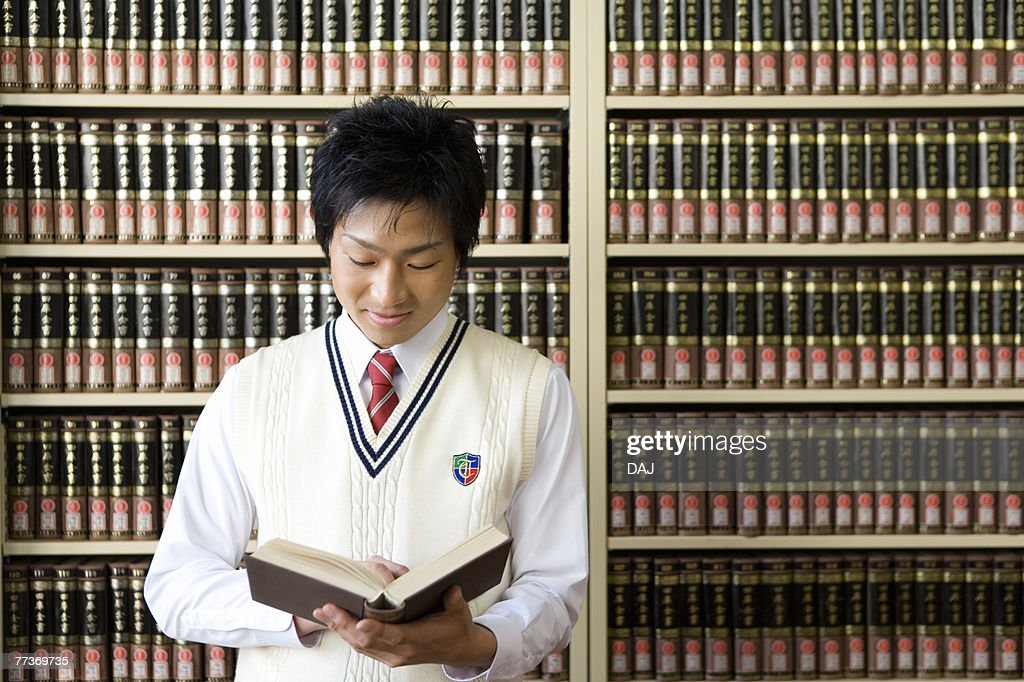 Teenage boy reading a book in front of bookcase : Photo