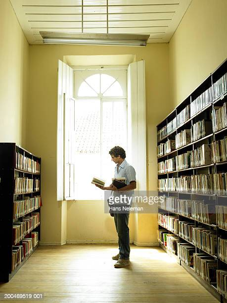 Teenage boy (15-17) reading book in library, side view
