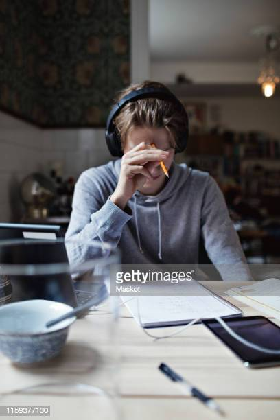 teenage boy reading book while using headphones at home - 集中 ストックフォトと画像