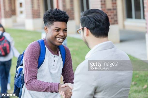 teenage boy receives congratulations from high school teacher - black people praying stock pictures, royalty-free photos & images