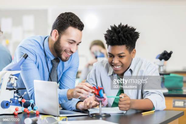 Teenage boy receives help from attentive science teacher
