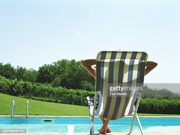 Teenage boy (13-15) relaxing in deckchair at edge of pool, rear view