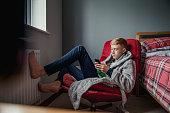 Teenage Boy Relaxing in his Bedroom