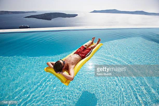 Teenage boy relaxing on raft in pool