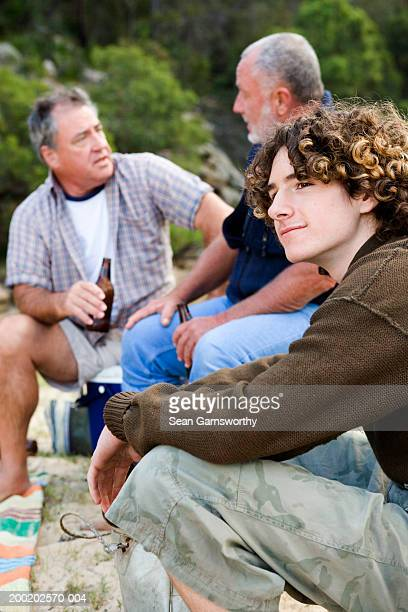 Teenage boy (16-18) relaxing outdoors, two mature men in background