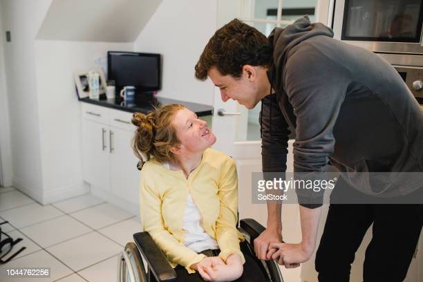 Teenage Boy Relaxing with Disabled Sister at Home