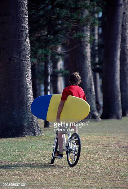 Teenage boy (15-17) ri8ding bicycle, carrying surfboard, rear view