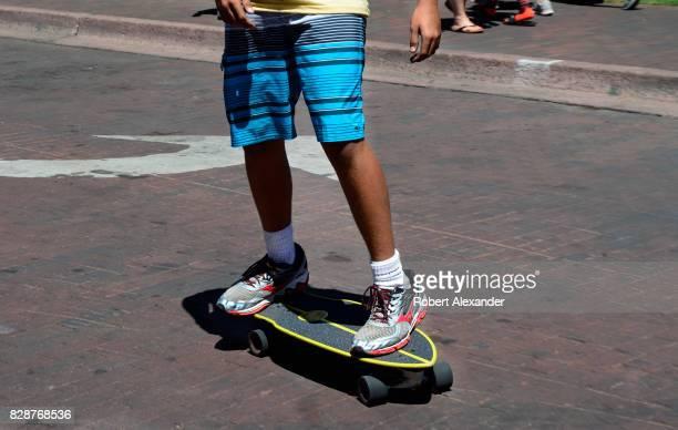 A teenage boy rides his skateboard along a street bordering the historic Plaza in Santa Fe New Mexico