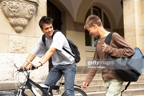 A teenage boy riding a bike while another one walks beside him.
