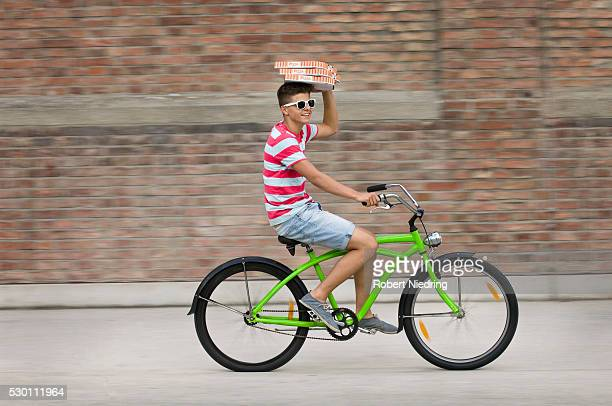 Teenage boy riding bicycle and holding pizza boxes