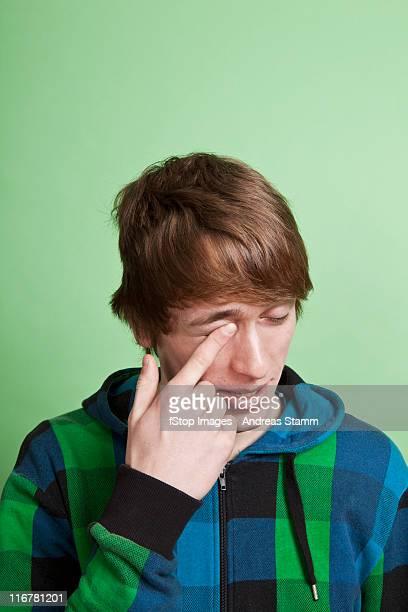 A teenage boy rubbing his eye with his finger, portrait, studio shot