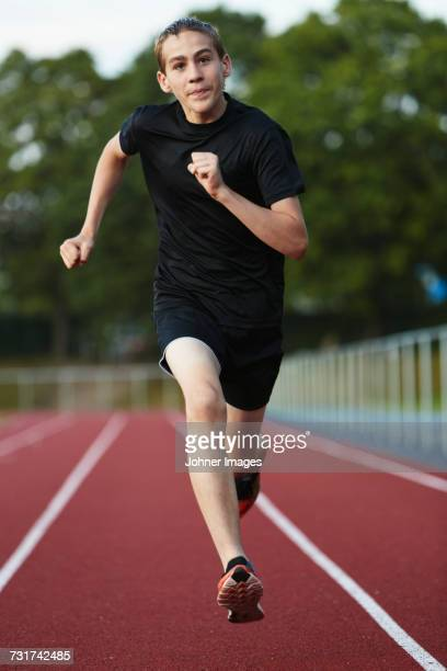 Teenage boy running in sports track