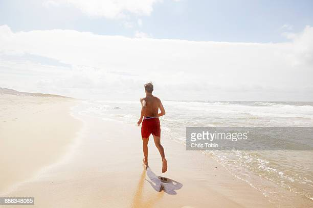 Teenage boy running on beach