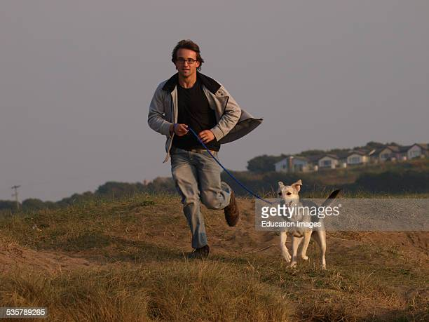 Teenage boy running over sand dunes with his dog Bude Cornwall UK