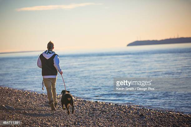 Teenage boy running with his rottweiler dog on the beach at point wornzof cook inlet and fire island in the background at sunset