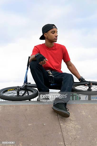 Teenage boy seating on a BMX Bike
