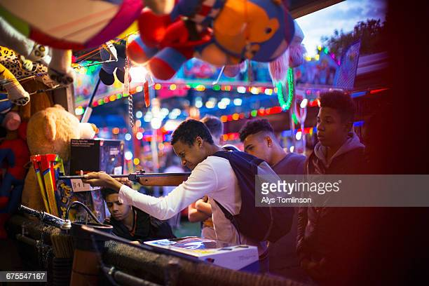 teenage boy shooting air rifle at fairground - one night stand stock-fotos und bilder