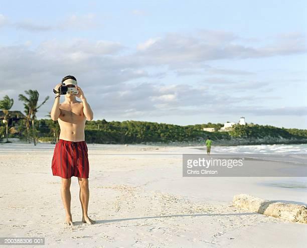 Teenage boy (15-17) shooting video at beach