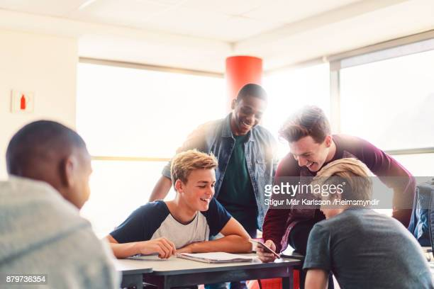 teenage boy showing mobile phone to friends - teenage boys stock pictures, royalty-free photos & images