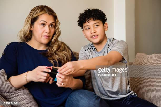 """teenage boy showing mother how to play video games in self-isolation, covid-19. - """"martine doucet"""" or martinedoucet foto e immagini stock"""