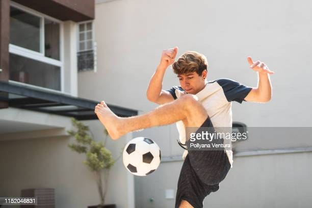 teenage boy showing off his football skills in the backyard of his house - play off stock pictures, royalty-free photos & images