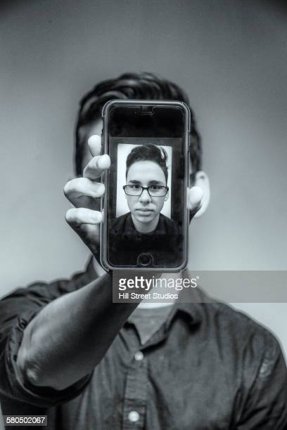 Teenage boy showing selfie on cell phone