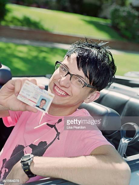 Teenage Boy Sits Holding an ID Card in the Front Seat of a Convertible Car