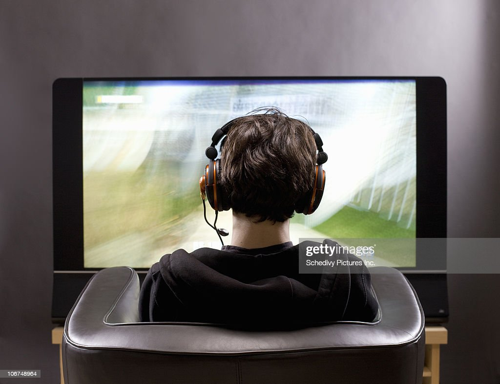 Teenage boy sits in front of TV playing video game : Stock Photo