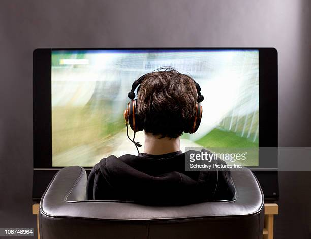 teenage boy sits in front of tv playing video game - gamer stock pictures, royalty-free photos & images