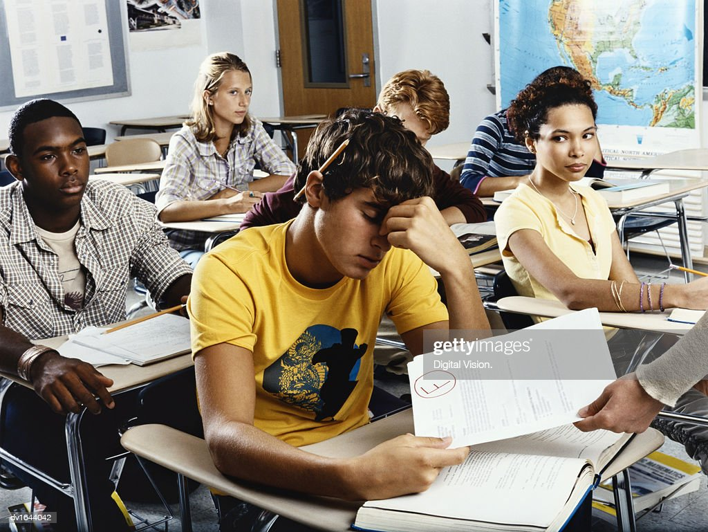 Teenage Boy Sits Looking Down in Embarrassment as he is Given a Failed Exam Paper : Stock Photo