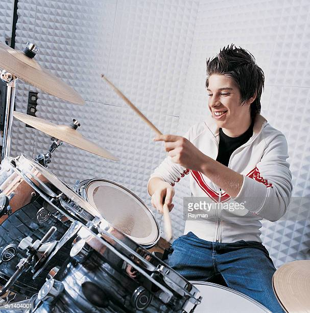 Teenage Boy Sits Practising the Drums in a Recording Studio