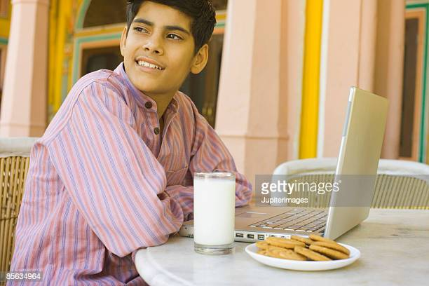 Teenage boy sitting at table in front of milk and cookies