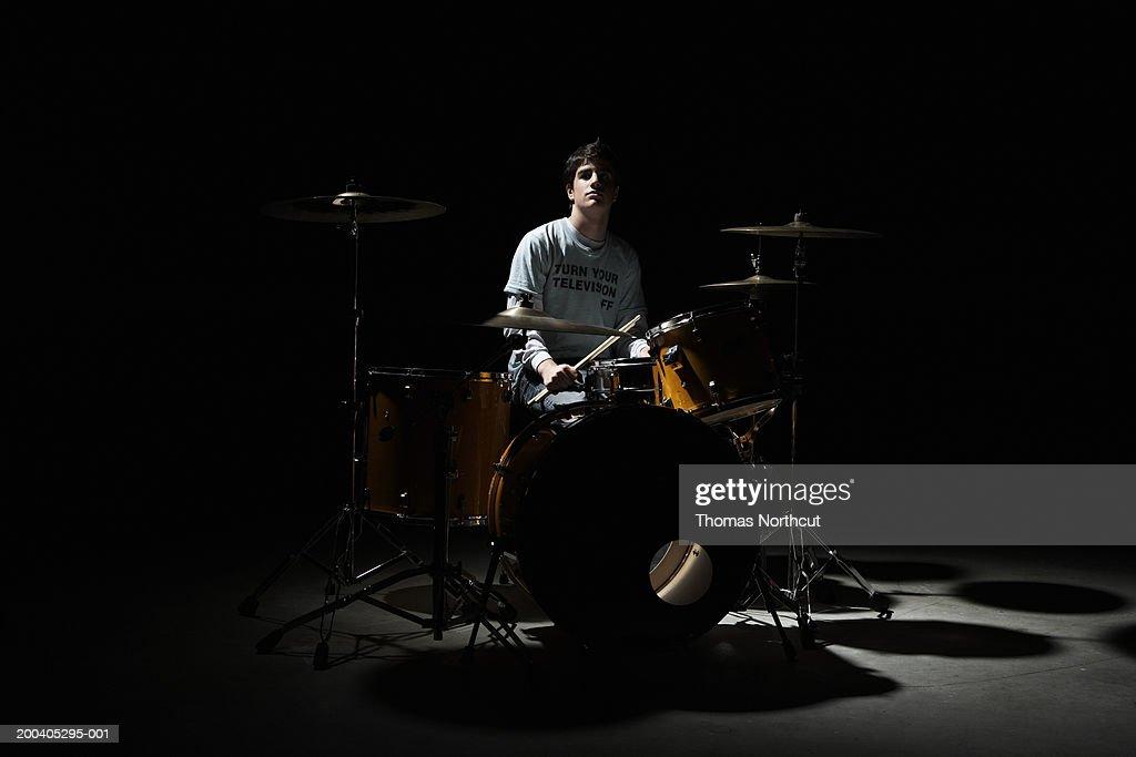 Teenage boy (13-15) sitting behind drum kit, portrait : Stock Photo