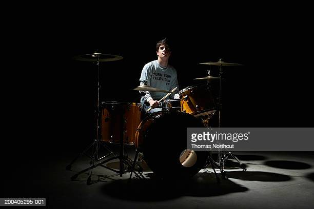 teenage boy (13-15) sitting behind drum kit, portrait - drum kit stock photos and pictures