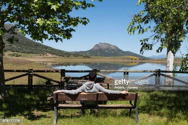 A teenage boy sitting looking at a lake