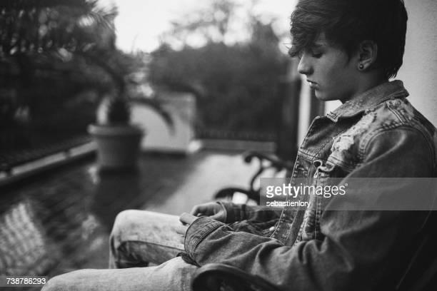 Teenage boy sitting on a bench