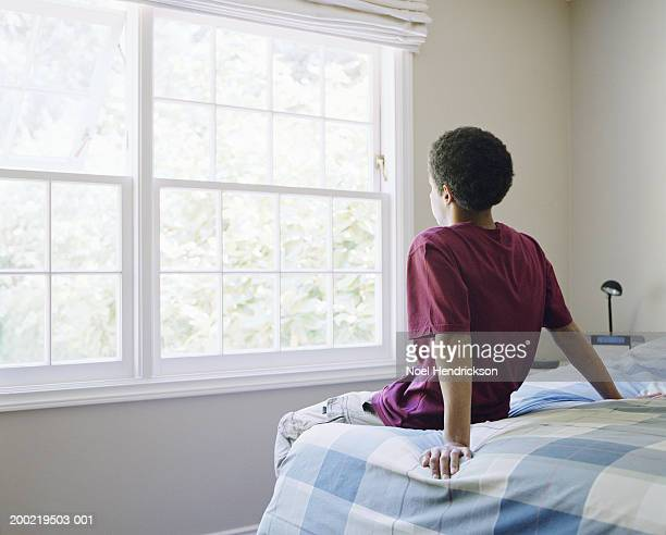 Teenage boy (16-18) sitting on bed, looking out window, rear view