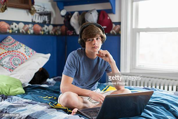Teenage boy sitting on bed with laptop computer