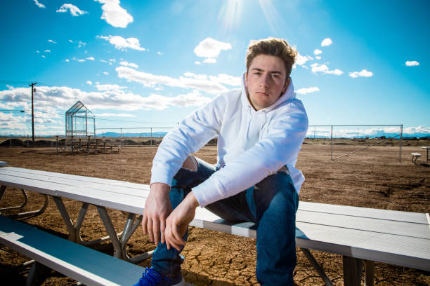 Teenage boy sitting on bench in front of an urban baseball field looking at camera.