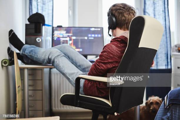 Teenage boy sitting on chair with feet up by computer while listening music through headphones at home