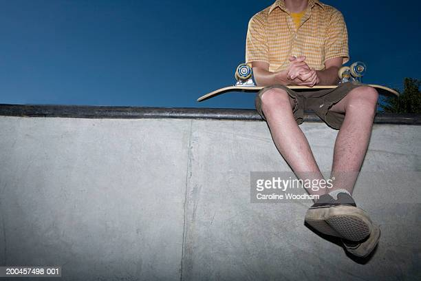 Teenage boy (13-15) sitting on edge of halfpipe, low section