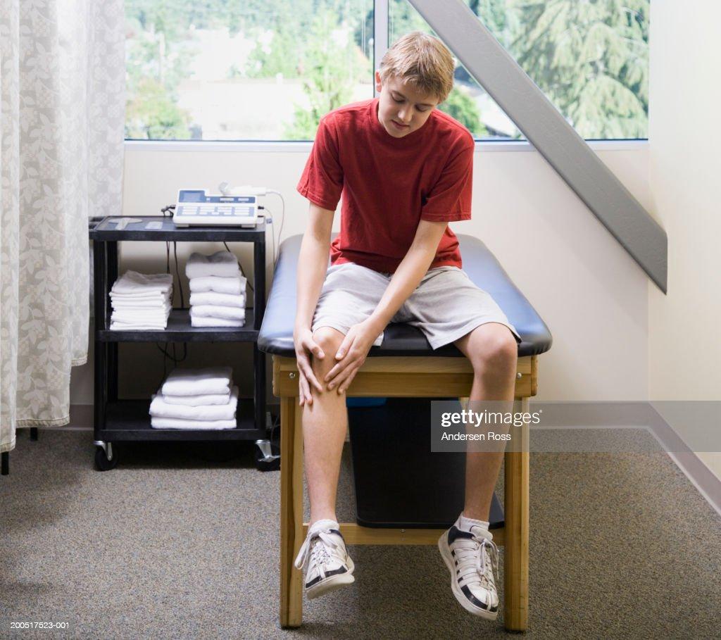 Teenage Boy Sitting On Examination Table Rubbing Knee