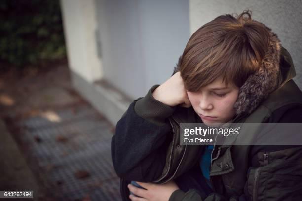 Teenage boy sitting on floor with sulking expression
