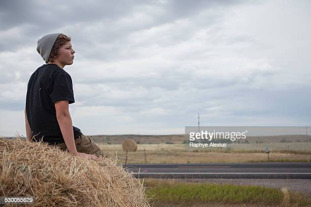 Teenage boy sitting on haystack, South Dakota, USA