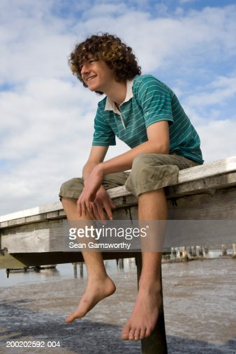 Teenage Boy Sitting On Jetty Smiling Low Angle View Stock