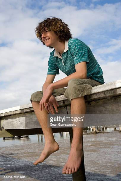 Teenage boy (16-18) sitting on jetty, smiling, low angle view