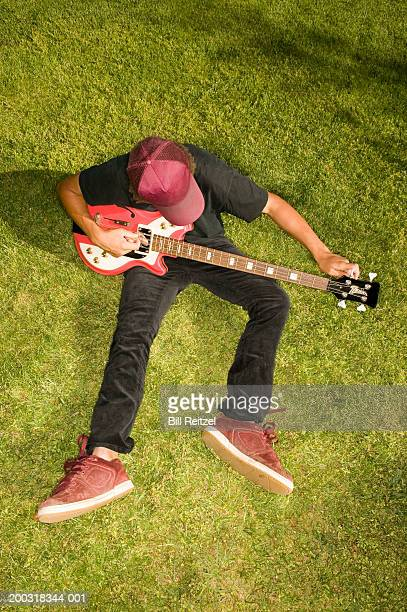 Teenage boy (13-15) sitting on lawn, tuning bass guitar, elevated view