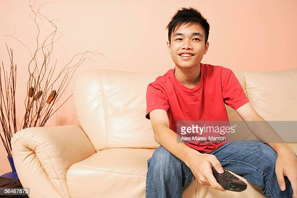 Teenage boy sitting on sofa, holding remote control