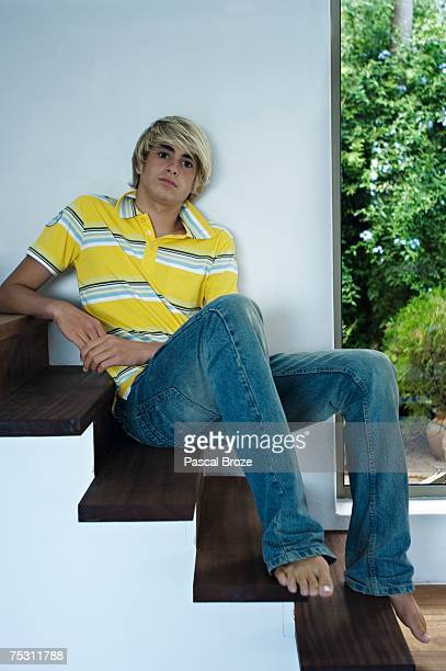 teenage boy sitting on stairs - teen boy barefoot stock photos and pictures