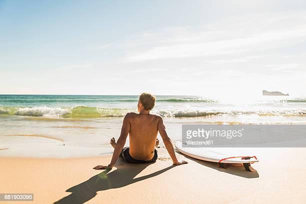 Teenage boy sitting on surfboard at the sea